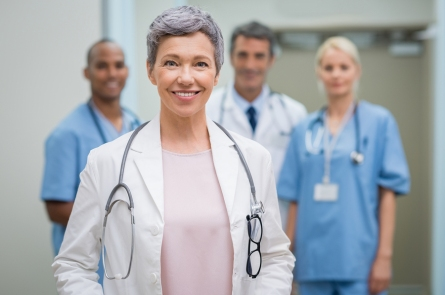 Portrait of smiling woman doctor standing in hospital with team in background. Senior female doctor in front of her medical staff. Team of medical professionals looking at camera.